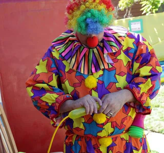 A person in a colorful clown costume making balloon animals