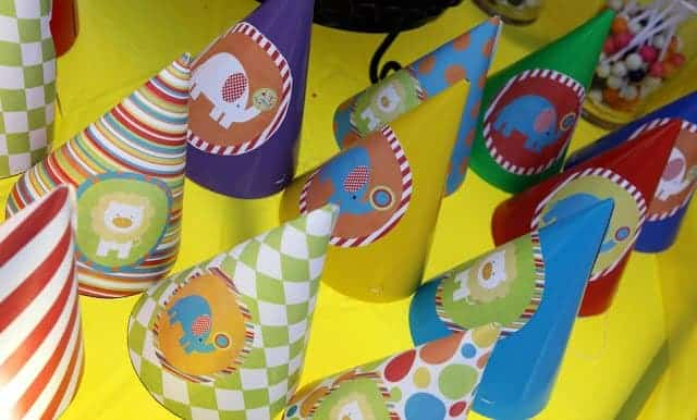 Party hats with cartoon circus animals on a yellow table