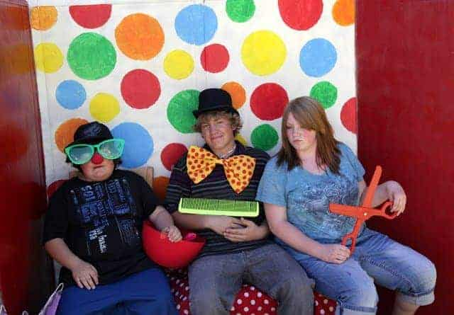 Three people in a circus-themed photo booth with props and a polka dotted wall backdrop