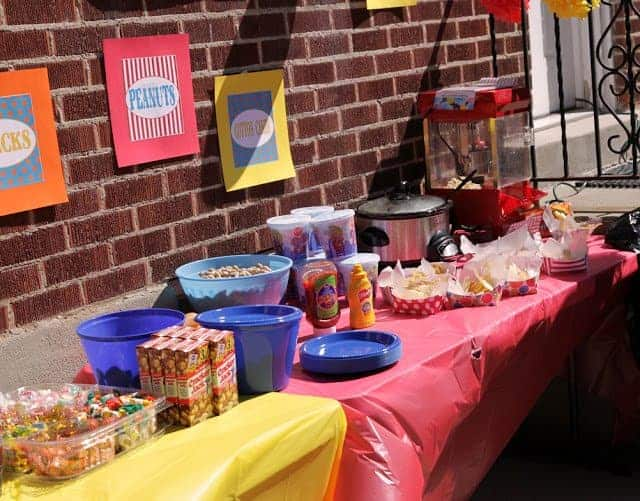 A buffet table filled with circus-themed foods and snacks, including Cracker Jack, peanuts and candy