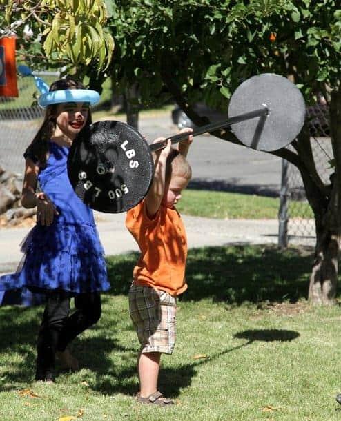 A little boy holding up a pretend 500-lb weight barbell