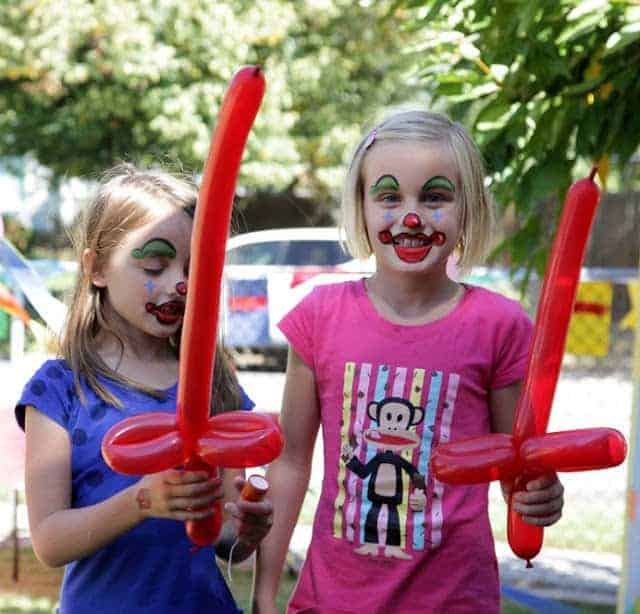 Two girls with clown face paint and red balloon swords