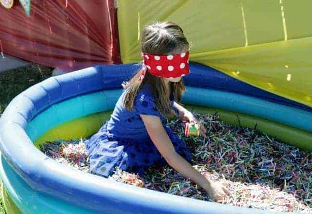 A little girl with a blindfold in an inflatable pool filled with shredded paper