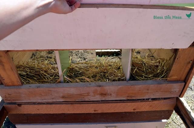 A wooden chicken coop with 3 nesting boxes with hay