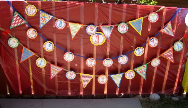 Circus-themed happy birthday flag banner in front of a red backdrop
