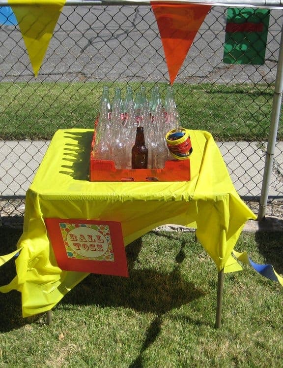 Clear glass bottles on a table with yellow tablecloth for Bottle Toss game