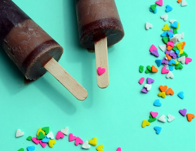 Two fudge pops laying on an aqua background surrounded with heart-shaped sprinkles