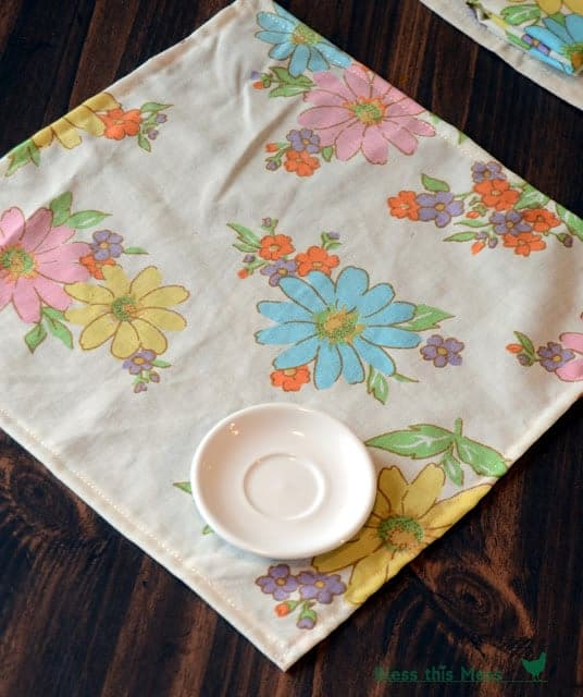 A colorful floral-printed cloth napkin on a table with a white saucer on it