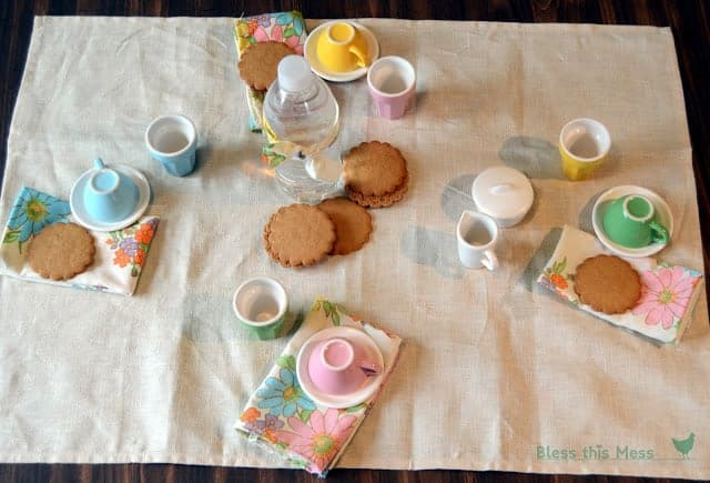 Four colorful tea cups and saucers with floral cloth napkins and a stack of cookies in the center