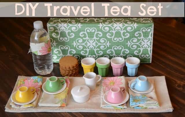 Title image for DIY Travel Tea Set  and a set of colorful tea cups and saucers on floral napkins and a stack of cookies
