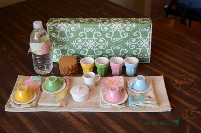 A green and white decorative box with a colorful tea set, napkins and cookies displayed in front