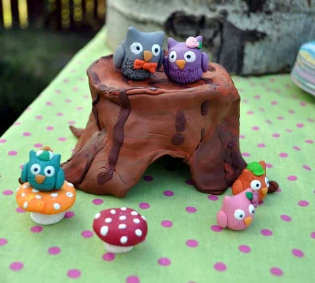 Owl-themed party decorations with owls on a log