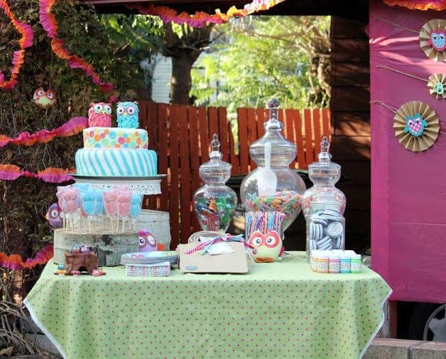 A table with owl-themed birthday decorations and treats