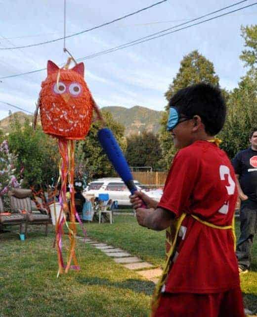 A child striking an owl pinata with a bat