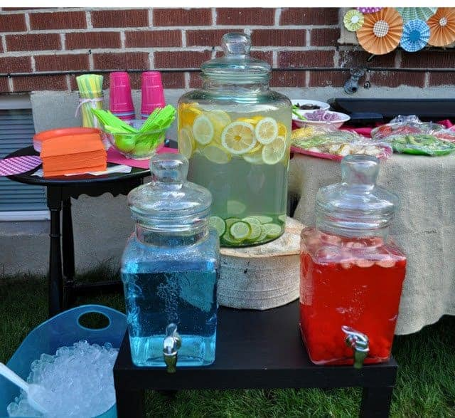 A display of colorful drinks in glass dispensers, cups, and ice