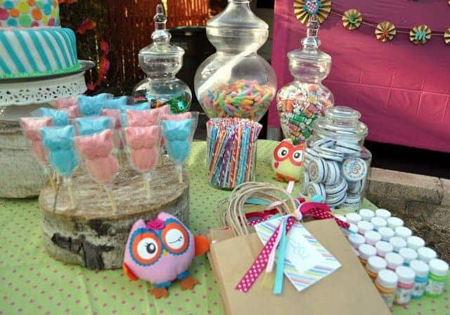 A table with owl-themed candy and party favors