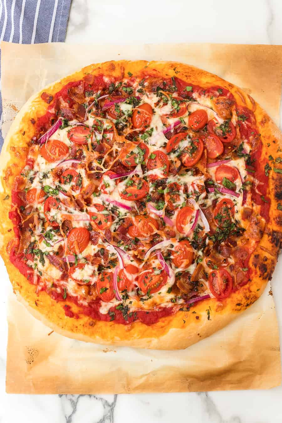 Homemade pizza dough topped with bacon, cheese, tomatoes, and herbs is the perfect pizza to make tonight. Your whole family will love it! #pizza #homemadepizza #tomatobaconpizza