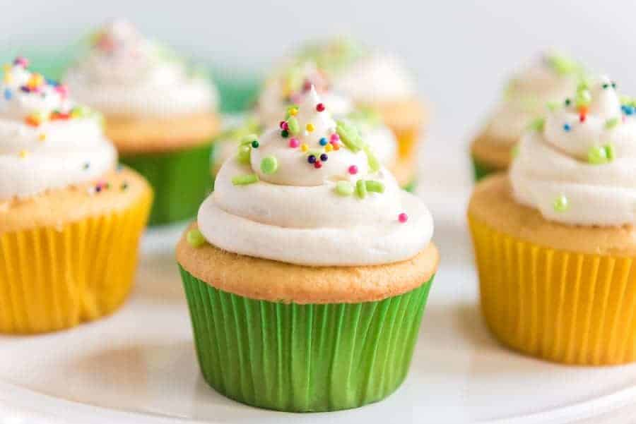 A cupcake that has been iced and sprinkled is in the foreground with other decorated cupcakes in the background.