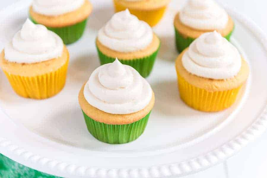 An iced cupcake is shown in the foreground with six other cupcakes in the background on an elegant white plate.