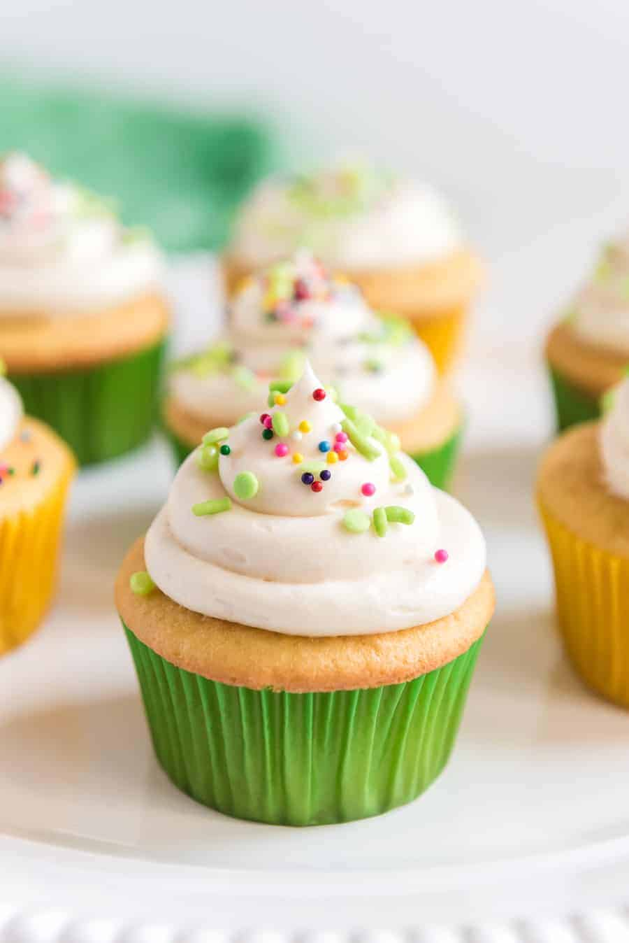 Up close shot of a cupcake that has been iced with vanilla frosting and a variety of sprinkles.