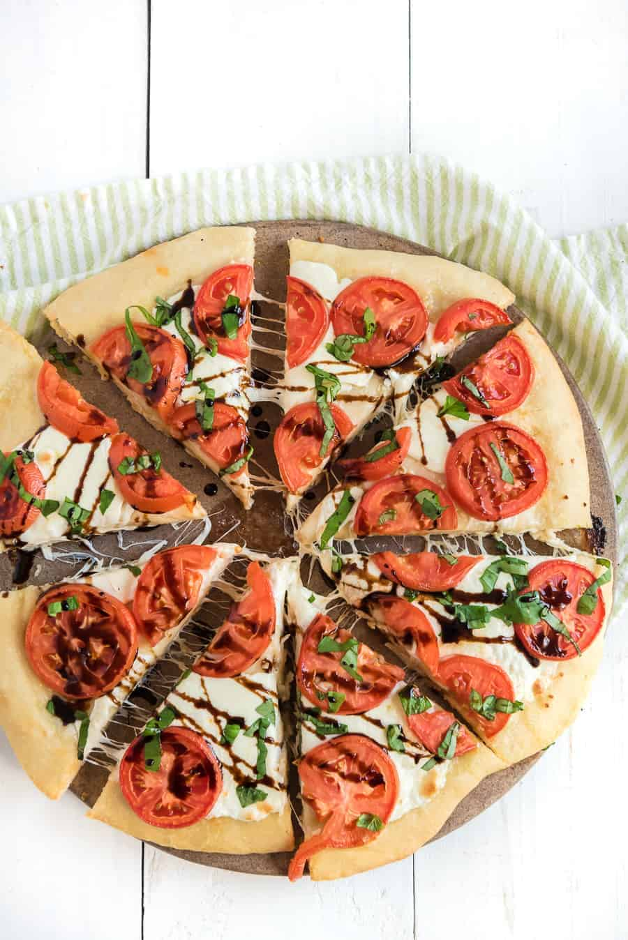 This easy margherita pizza recipe is made of a simple homemade pizza dough with fresh tomato, mozzarella, and basil for a fun and casual meal you can make at home. It's the ideal meal for a busy weeknight or a low-key movie night on the weekend, and it's beyond simple to make from scratch with minimal ingredients. #pizza #margheritapizza #margheritapizzarecipe #pizzarecipe #homemadepizza #homemadepizzadough #pizzadoughrecipe