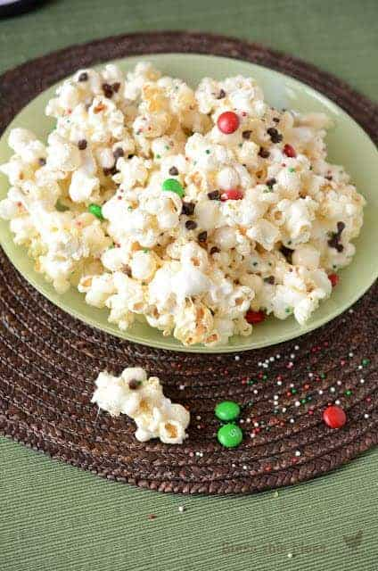 popcorn in a bowl with some chocolates and sprinkles spilling out the side of the bowl