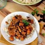 A white plate of rice topped with curried chicken with butternut squash and dried cherries