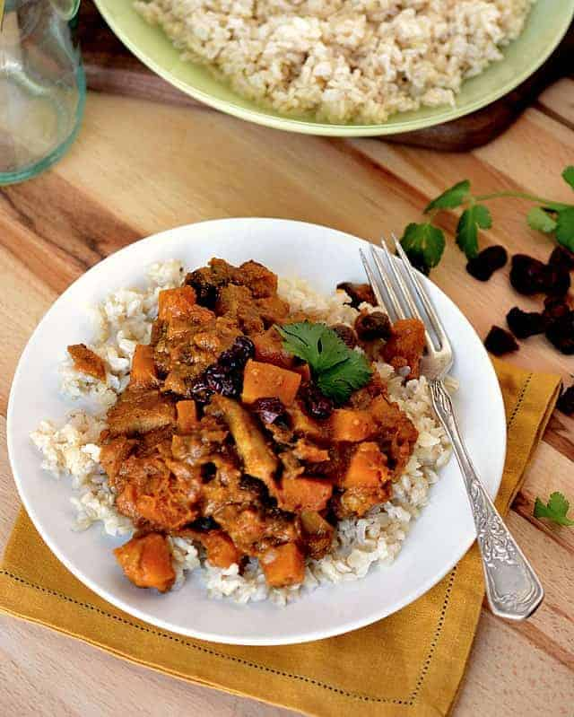 Curried Chicken over rice served on a white plate with a fork. A bowl of rice sits to the side.