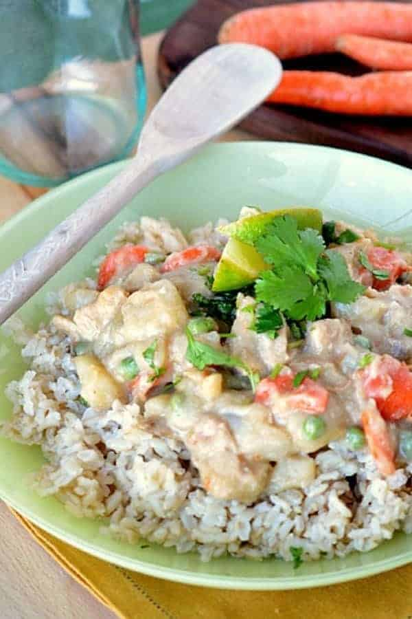 A bowl of chicken and vegetables in Thai Green Curry sauce over rice with fresh cilantro and a lime wedge