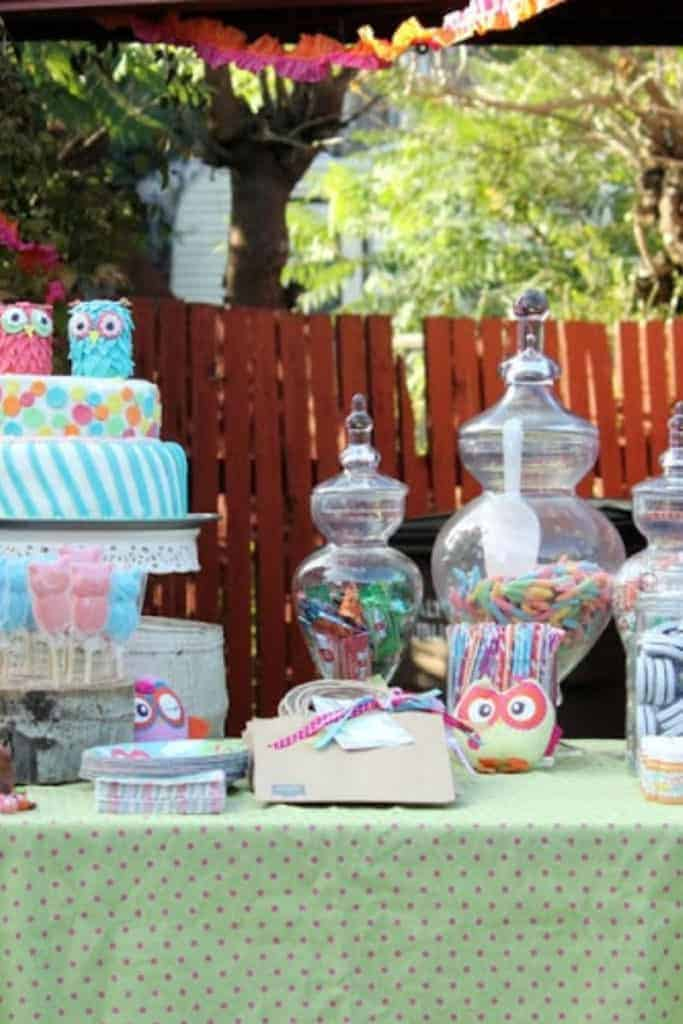 A party table with owl-themed decorations, cake, and jars of candy