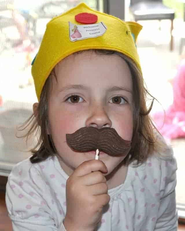a girl with a chocolate mustache on a stick