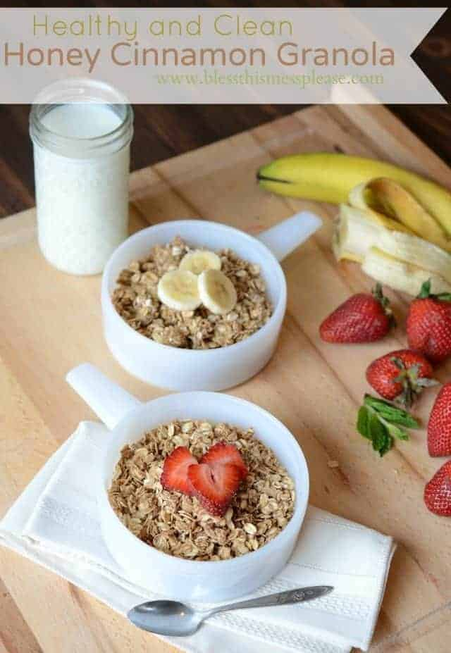 clean granola in two bowls with banana and strawberries on top