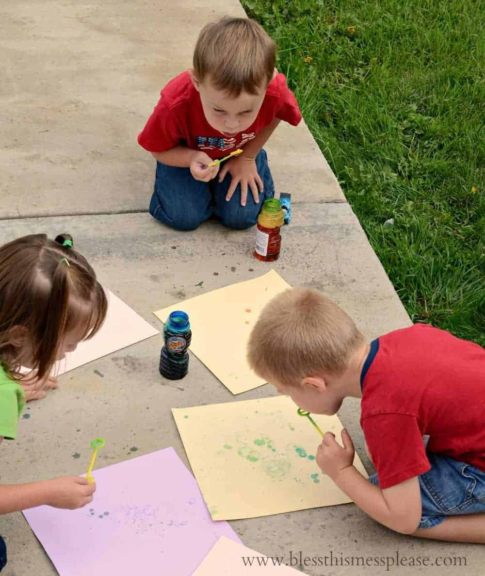 kids blowing bubbles onto paper