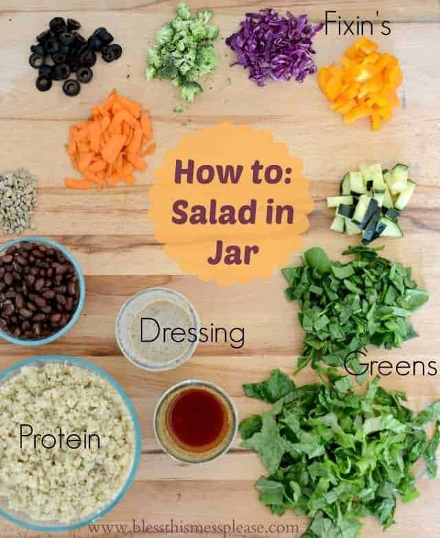 Salad greens, dressings, and other fixings on a wooden cutting board.