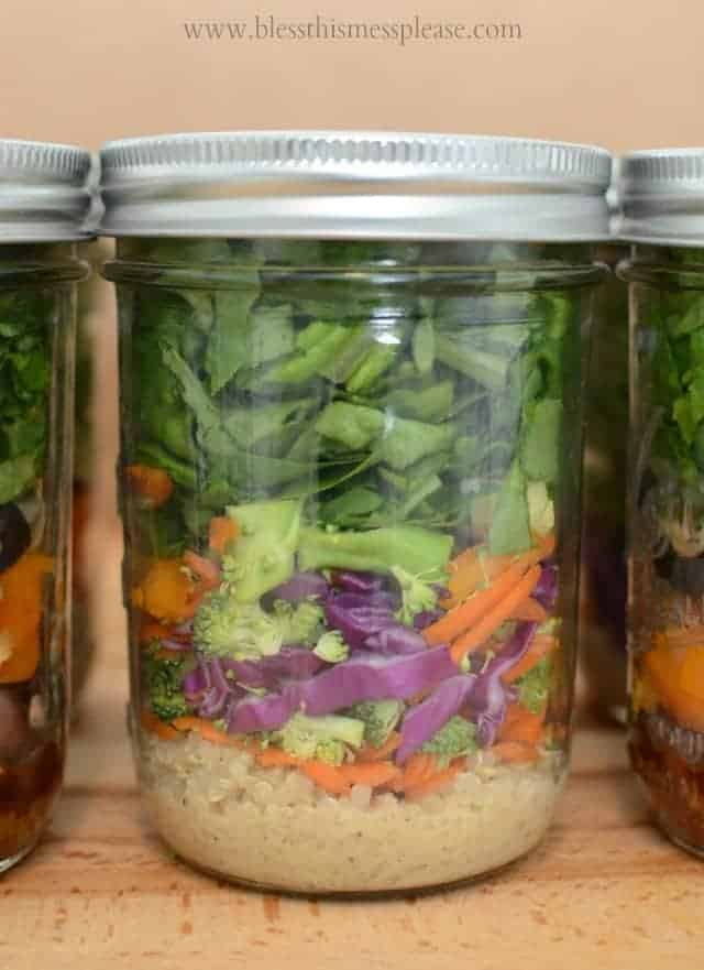 a closeup shot of a salad showing its layers of red cabbage, orange carrots, and green spinach