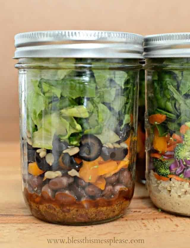 A closeup shot of a salad in a jar showing its colorful layers of beans, peppers, and lettuce