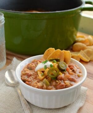 This Loaded Nacho Supreme Chili is awesome! Sausage, beans, rice, cheese, and all kinds of other goodness all in one bowl served with chips and your favorite nacho toppings. It's like eating nachos with a spoon.