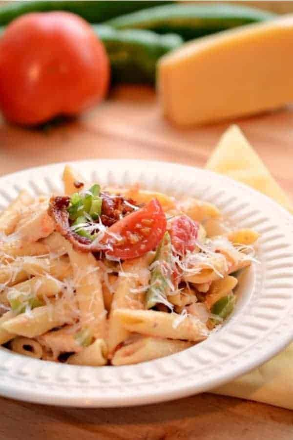 A round white bowl of penne pasta with bacon, tomato, green peppers, creamy Alfredo sauce and grated Parmesan cheese