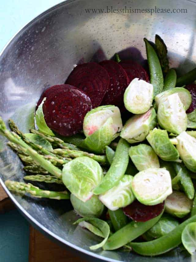 spring vegetables with oil and salt mixed together in a bowl