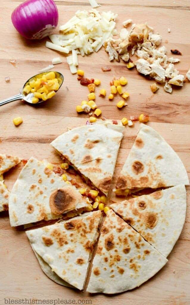 tortillas, onion, cheese, corn, and chicken on a cutting board