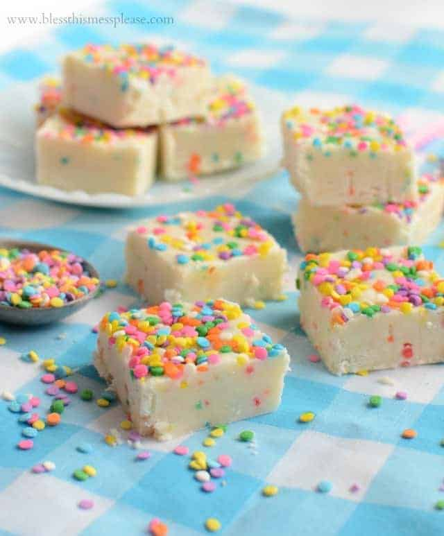 White fudge squares with rainbow sprinkles on a blue and white checked cloth