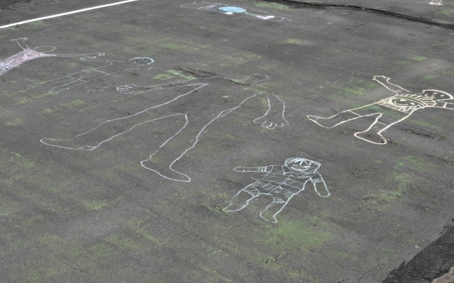 Sidewalk chalk drawings of adults and children