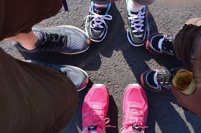 Looking down at the lower legs and sneakers of four people standing in a close circle