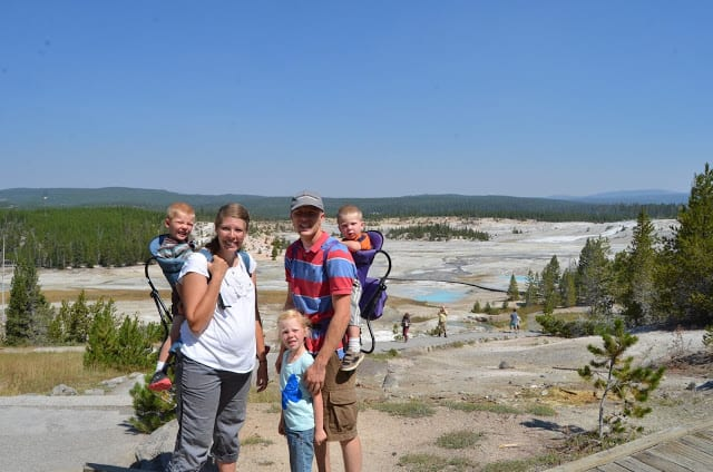 A family atop a hiking trail with two children in backpack carriers and an elementary aged child