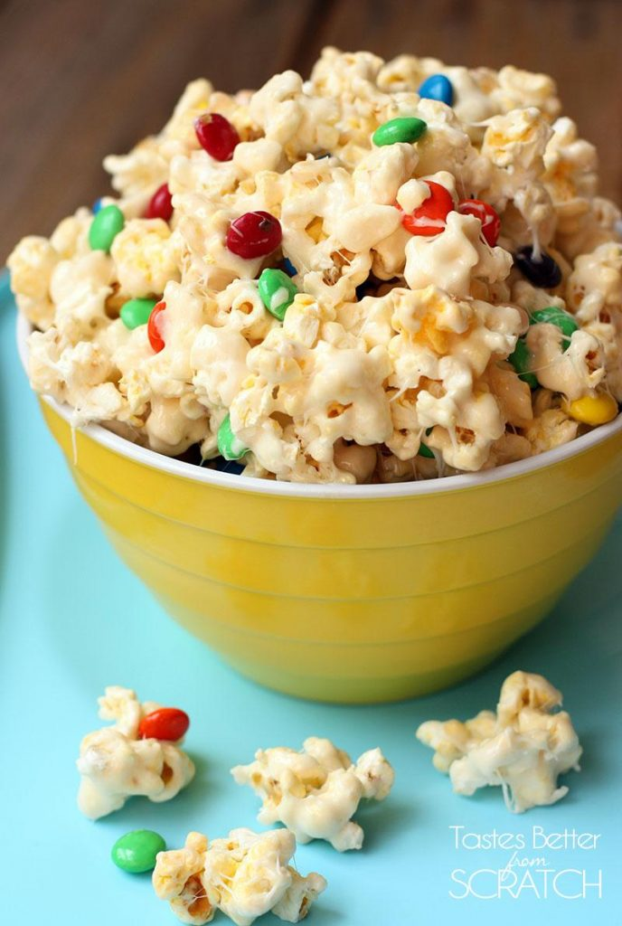 a bowl of white chocolate covered popcorn in a yellow bowl.