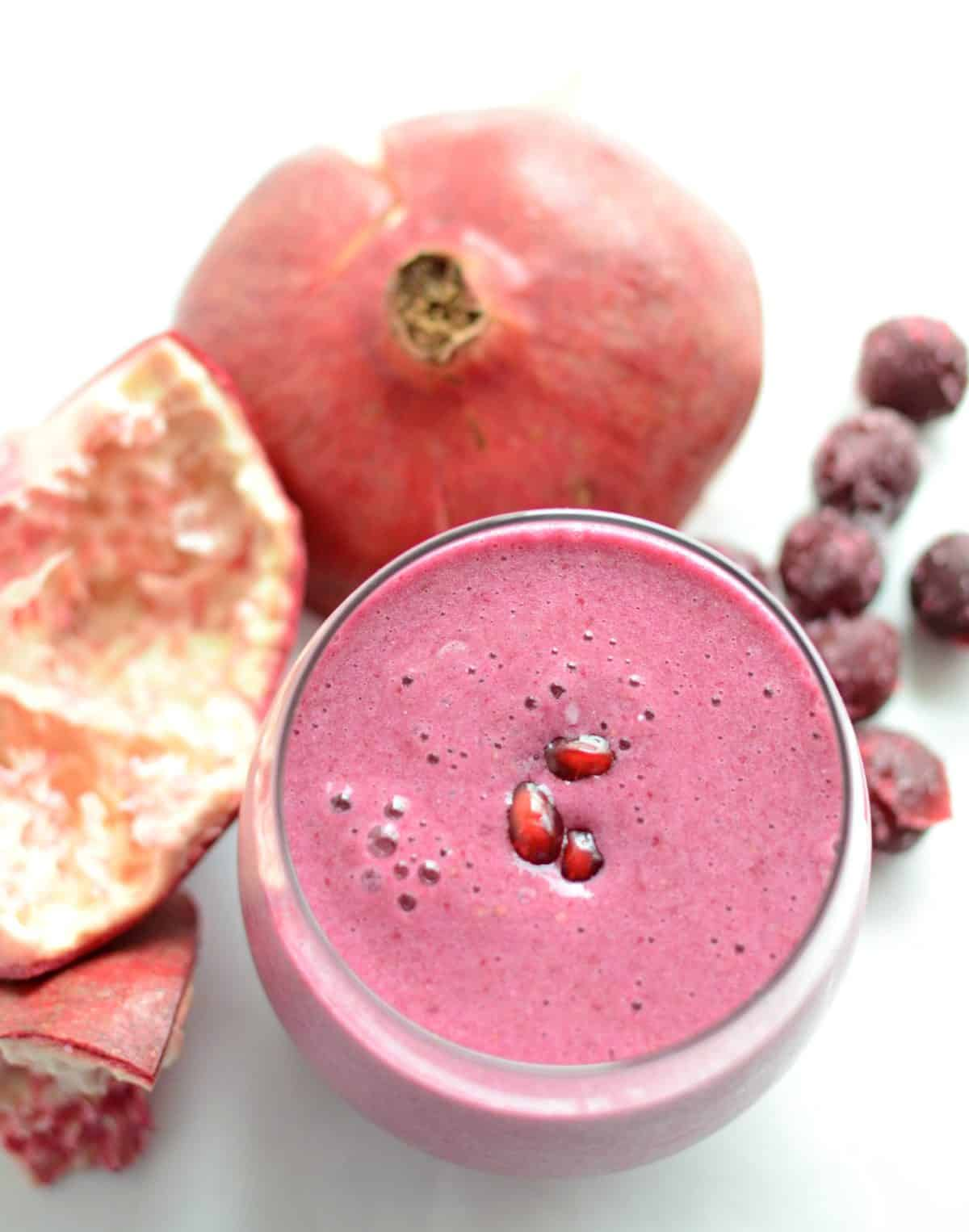 a pink smoothie in a glass cup with a pomegranate and pomegranate seeds to the side