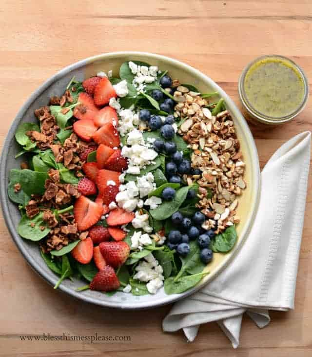 Bowl of berry spinach salad with a cup of citrus poppy seed dressing