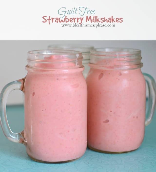 Two pink strawberry milkshakes in mason jars with handles