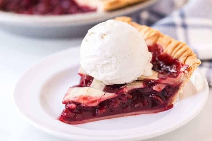 slice of cherry pie with scoop of vanilla ice cream on round white plate