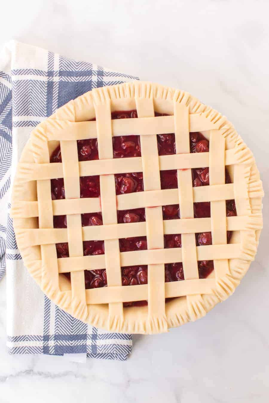 unbaked cherry pie with criss cross pie crust resting on blue and white checkered towel on white countertop